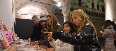 Adulti e bambini curiosano tra le bancarelle allestite al Castello Sforzesco (Fotogramma)