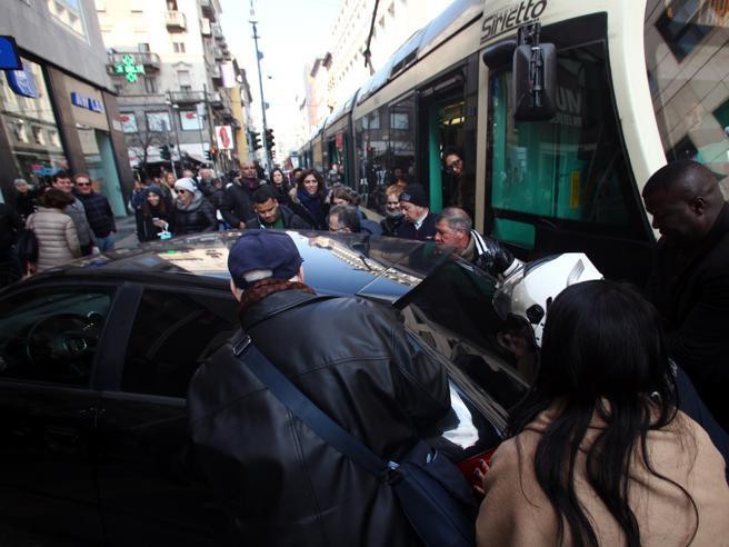 Folla spinge l'auto  ferma in sostaselvaggia e libera i binari del tram